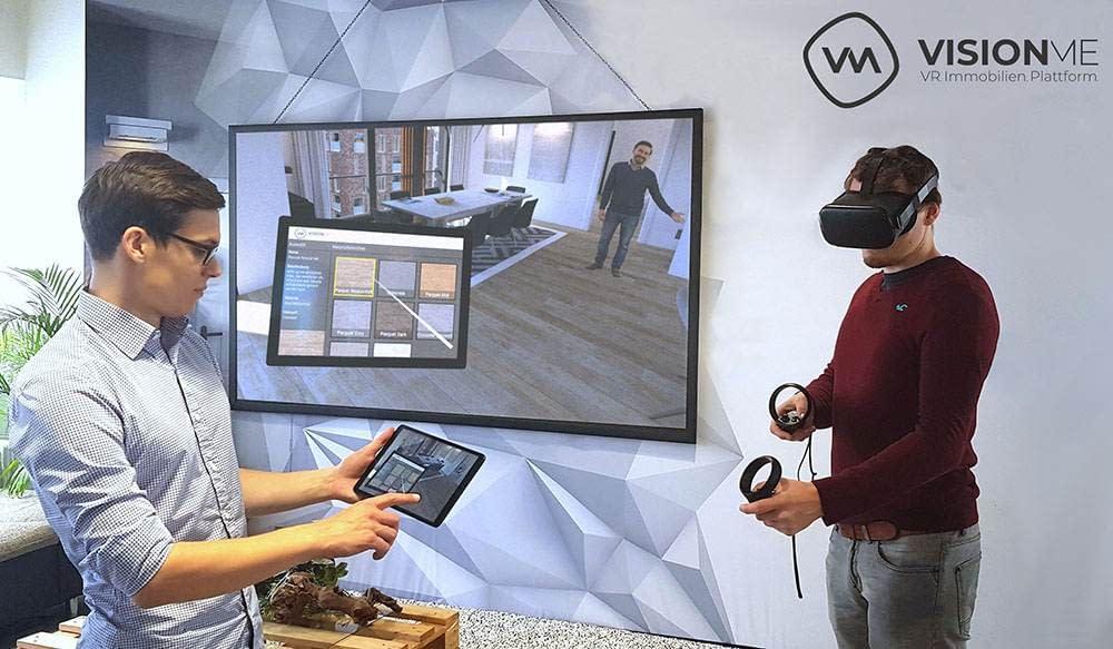 Visionme Geschäftsführer Florian Wenk und Dennis Dohmeier präsentieren den Immobilien Designer auf VR-Brille und Tablet mit Beamer im Hintergrund