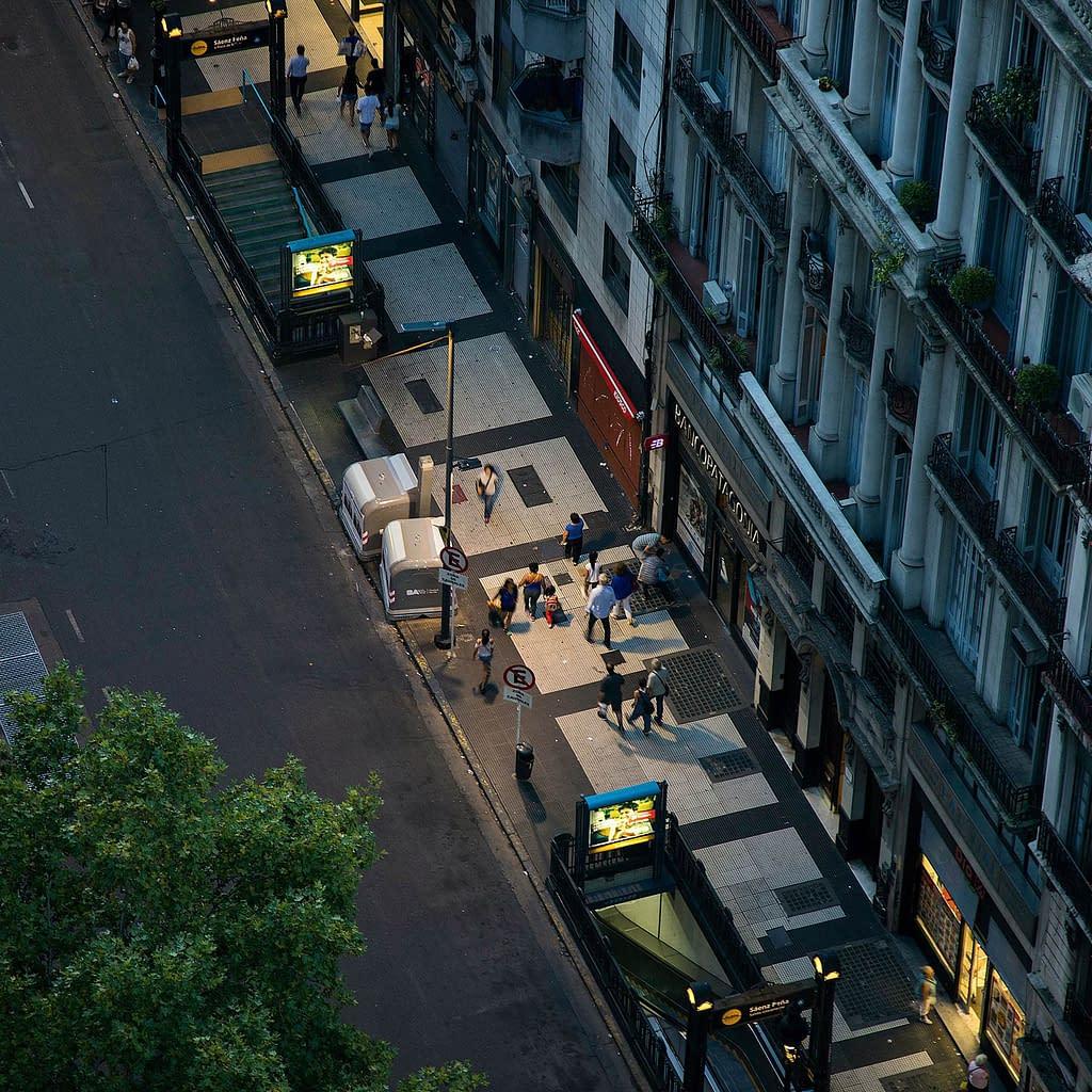 Straße im Abendlicht mit Passanten und Haltestellen