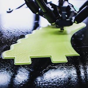 3D Drucker im Einsatz zum drucken eines grünen Architekturbestandteils.